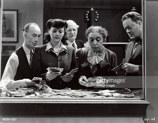 Actors count money in a scene from the film 'Inside the Law' 1942 Pictured are from left Danny Duncan Luana Walters Lafe McKee Rose Plummer and...