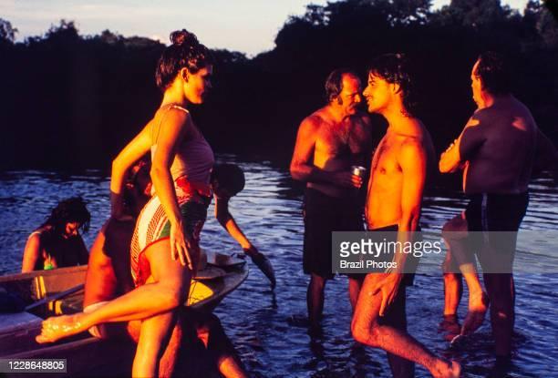 Actors Cristiana Oliveira, Angelo Antonio, Claudio Marzo, Antonio Petrin and others relax at riverside during break on recordings of Pantanal,...