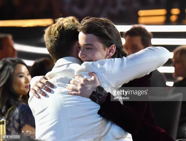 Actors Dacre Montgomery and Noah Schnapp embrace at the 2018 MTV Movie And TV Awards at Barker Hangar on June 16 2018 in Santa Monica California