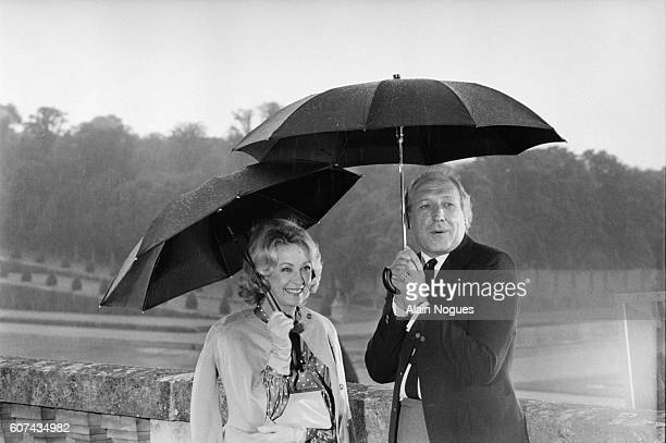 Actors Danielle Darrieux and Georges Wilson hold umbrellas on the set of the television show Les Jardins du Roi or The King's Gardens They are...