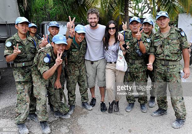 Actors Demi Moore and Gerard Butler pose with a group of Japanese UN soldiers during a visit to a camp for internally displaced persons managed by...