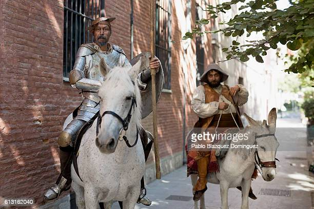 Actors depicting Don Quijote de la Mancha and Sancho Panza perform as they ride a horse and donkey along the streets during the Cervante's Week on...