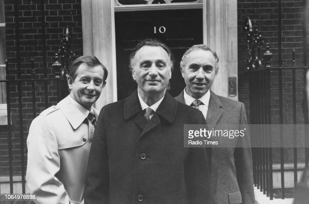 Actors Derek Fowlds Paul Eddington and Nigel Hawthorne outside 10 Downing Street in a scene from the television sitcom 'Yes Minister' London October...