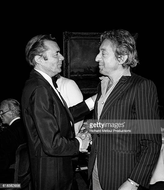 Actors Dirk Bogarde and Serge Gainsbourg shake hands. The two are attending the 36th Cannes Film Festival.