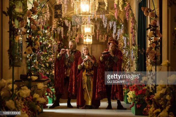 Actors dressed as a fairytale storytellers play horns in Chatsworth House which has been decorated for their Christmas season in various fairy tale...