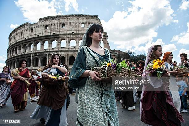 Actors dressed as ancient Roman maids march in front of the Coliseum in a commemorative parade during festivities marking the 2766th anniversary of...