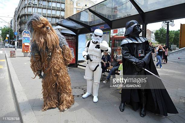 Actors dressed as characters from the science fiction film Star Wars, stand at a bus stop front of the Star Wars convention venue in Belgrade on June...