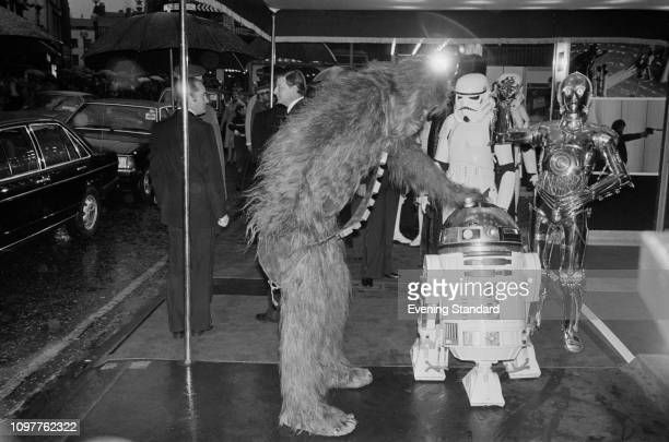 Actors dressed as fictional characters Chewbacca R2D2 and C3PO who all appear in the Star Wars franchise attend the royal premiere of 'The Empire...