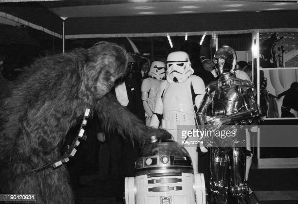 Actors dressed as fictional characters Chewbacca, R2-D2, C-3PO, and stormtroopers, who all appear in the Star Wars franchise, attend the royal...