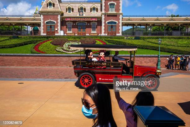 Actors dressed as Mickey and Minnie Mouse wave to visitors at Walt Disney Co's Disneyland Resort on June 18 2020 in Hong Kong China
