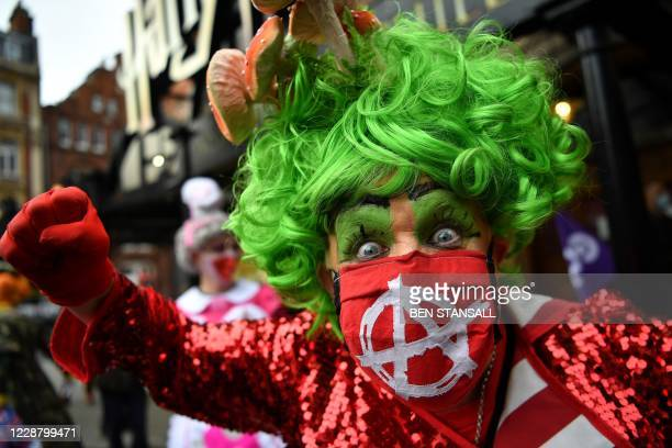 Actors dressed as pantomime Dames take part in a protest march towards the Houses of Parliament in London on September 30 to highlight the impact the...