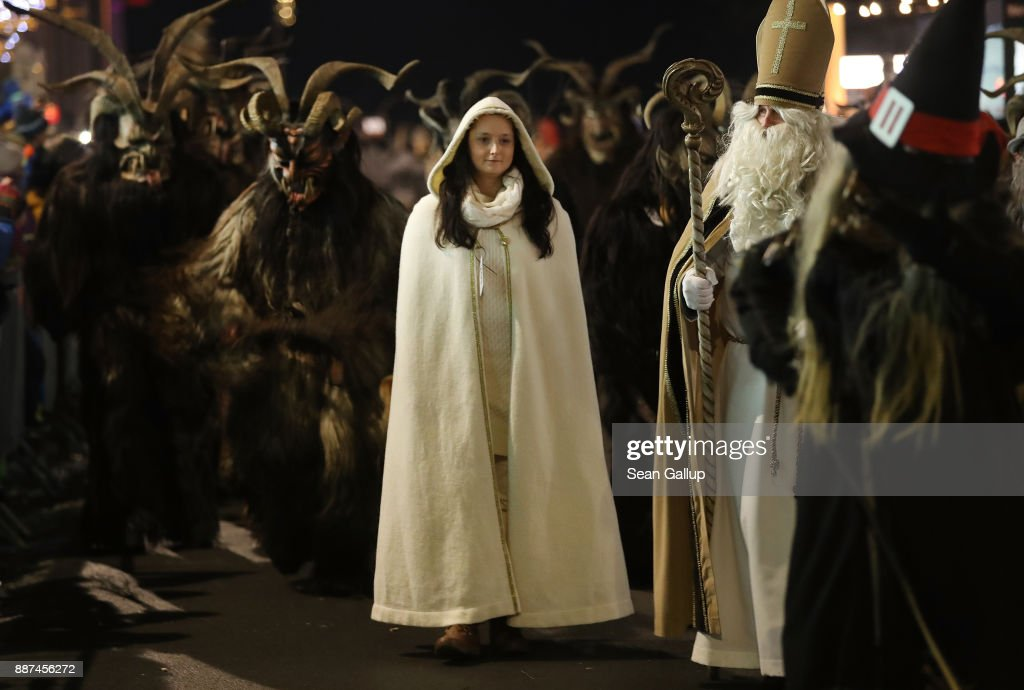 Actors dressed as Saint Nicholas and an angel lead a group of Krampus creatures during the annual Krampus parade on Saint Nicholas Day on December 6, 2017 in Sankt Johann im Pongau, Austria. Several hundred Krampus creatures from the region took part in this year's Sankt Johann parade. Krampus traditionally accompanies Saint Nicholas and angels in a house to house procession to reward children who have been good and warn those who have not, though in recent decades Krampus parades have become an intrinsic part of local folklore and take place throughout the end of November and into the first half of December in the alpine regions of Germany, Austria and Italy. Krampus usually wears large cowbells on his back that he rings by shaking his hips to ward off the evil spirits of winter. He also carries a switch made of branches or animal hair that he uses to whip bystanders.