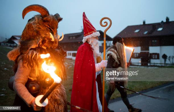 Actors dressed as Saint Nicholas and Klausen, a locally known and traditional figure, arrive to welcome children and parents in their cars at a Saint...