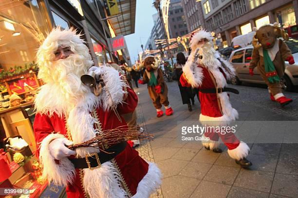 Actors dressed as Santa Claus and reindeer greet shoppers outside a department store on December 11 2008 in Berlin Germany German retailers hoping...