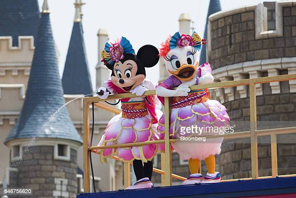Actors dressed as the characters Minnie Mouse left and Daisy Duck perform in front of the Cinderella Castle during the Disney Natsu Matsuri event at...