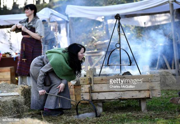 Actors dressed as villagers light a fire as they take part in the reenactment of the landing of Saint Patrick on Irish shores at Inch Abbey on March...