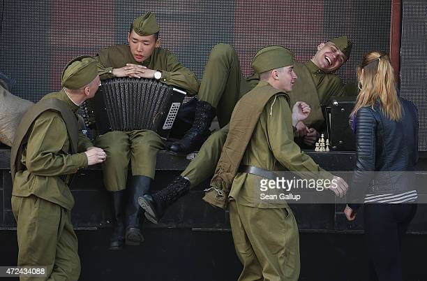 Actors dressed as World War II Soviet Red Army soldiers relax in between rehearsals at Red Square ahead of celebrations to mark the 70th anniversary...