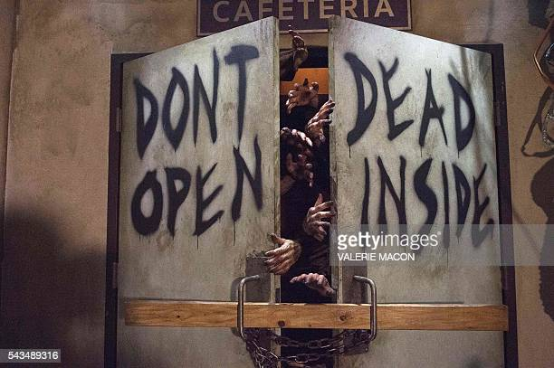 Actors dressed as zombies act at the Universal Studios Hollywood Opening of its New Permanent Daytime Attraction The Walking Dead in Universal City...