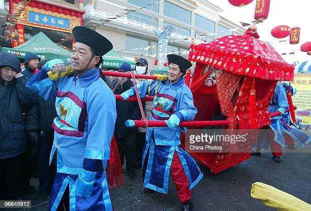 Actors dressed in ancient clothes carry a Chinese traditional sedan chair during a celebration to mark the upcoming Chinese New Year on January 22...