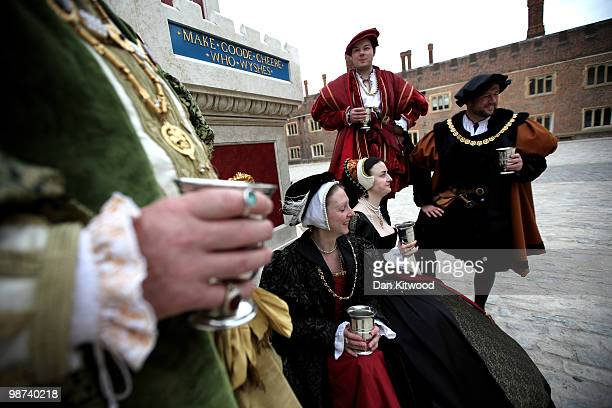 Actors dressed in historical costume gather around the newly unveiled wine fountain in the inner courtyard at Hampton Court Palace on April 29 2010...