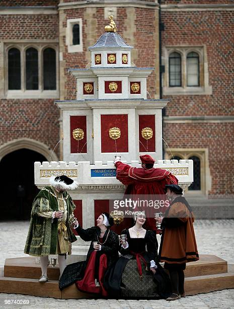 Actors dressed in historical costumes pose during a photocall at the newly unveiled wine fountain in the inner courtyard at Hampton Court Palace on...