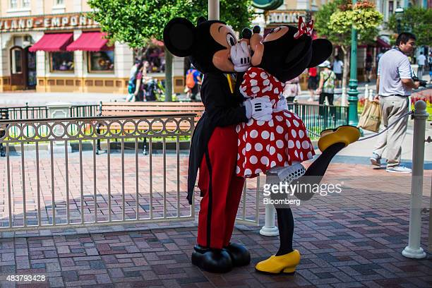 Actors dressed in Mickey Mouse and Minnie Mouse costumes kiss at Walt Disney Co's Disneyland Resort in Hong Kong China on Friday Aug 7 2015 Hong Kong...