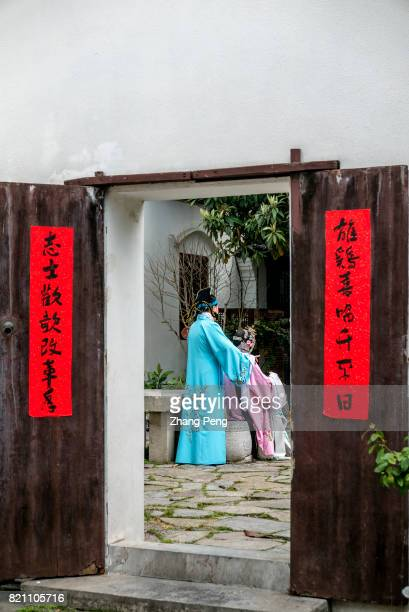 Actors dressed in traditional opera costumes are rehearsing in the garden of the residence of Ganxi family Ganxi was a literati in late Qing Dynasty...