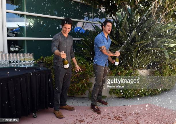 """Actors Dylan O'Brien and Tyler Posey from """"Teen Wolf"""" pop bottles of champagne to celebrate their final season backstage after their Hall H panel..."""