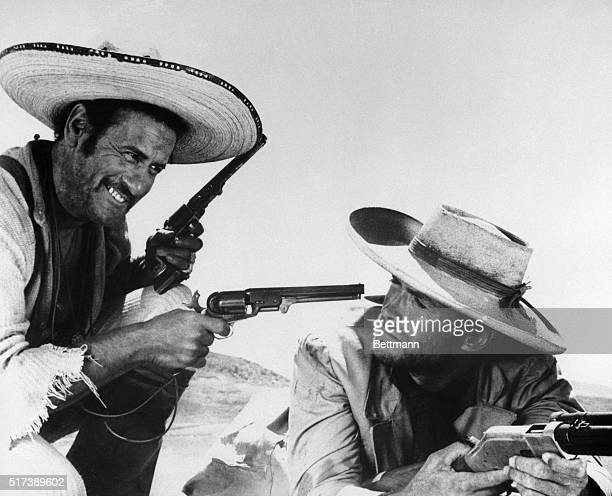 Actors Eli Wallach and Clint Eastwood hold guns during a scene from the 1966 film The Good the Bad and the Ugly