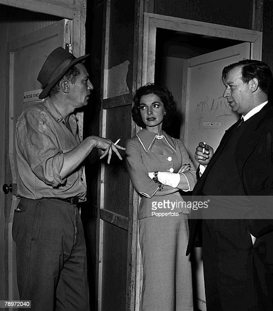 Actors Elizabeth Sellars and Peter Finch speaking with film director Leslie Norman during the making of the film The Shiralee at Ealing Studios 1957