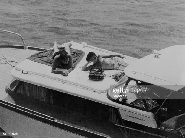 Actors Elizabeth Taylor and Richard Burton recline on the deck of a speedboat during a holiday in Ischia 18th June 1962 They had just completed work...