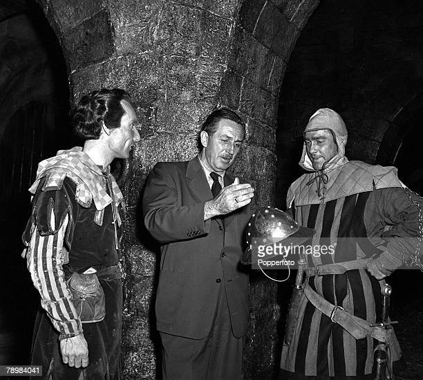 1951 Actors Elton Hayes and Richard Todd talk with American film producer cartoonist and animator Walt Disney on the set of the film 'Robin Hood'