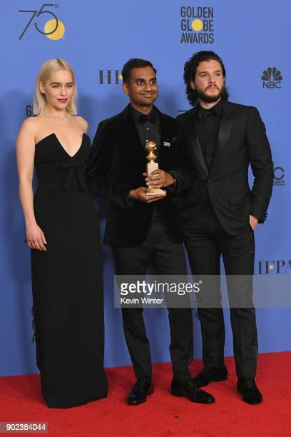 Actors Emilia Clarke and Kit Harington pose with Aziz Ansari and his award for Best Performance by an Actor in a Television Series Musical or Comedy...