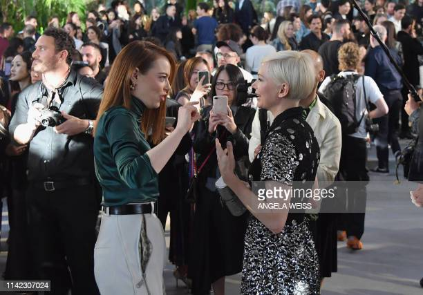 Actors Emma Stone and Michelle Williams attend the Louis Vuitton Cruise 2020 Fashion Show at TWA Flight Center at JFK Airport on May 8 2019 in New...
