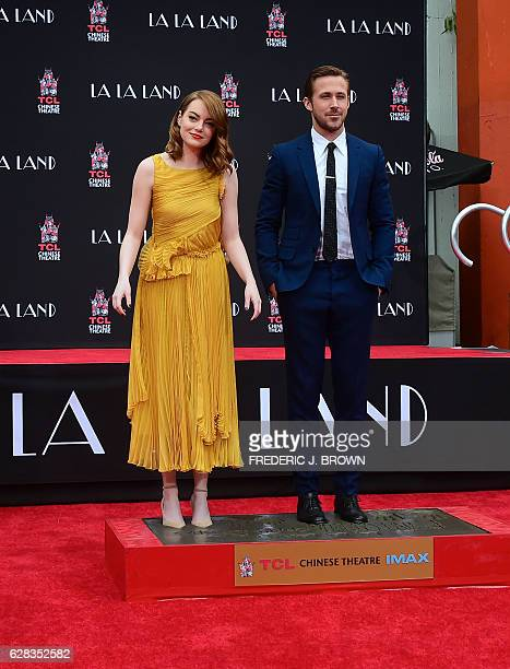 Actors Emma Stone and Ryan Gosling pose while standing on the block of cement at their Hand and Foot prints ceremony in front of the TCL Chinese...