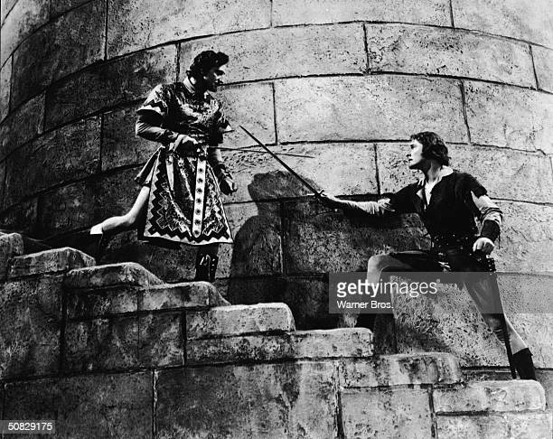 Actors Errol Flynn and Basil Rathbone duel on a castle stairwell in a still from the film 'The Adventures of Robin Hood' directed by Michael Curtiz...