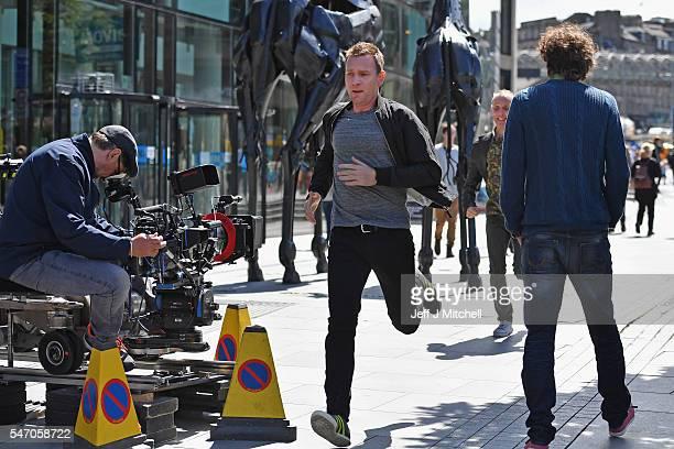 Actors Ewan McGregor and Ewan Bremner runs on the set of the Trainspotting film sequel on Princess Street on July 13 2016 in Edinburgh Scotland The...
