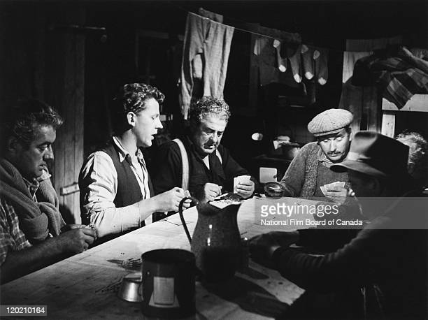 Actors Felix Leclerc Pierre Dufresne Paul Desmarteaux and Roland d'Amour are playing cards inside a log cabin during a scene from the National Film...