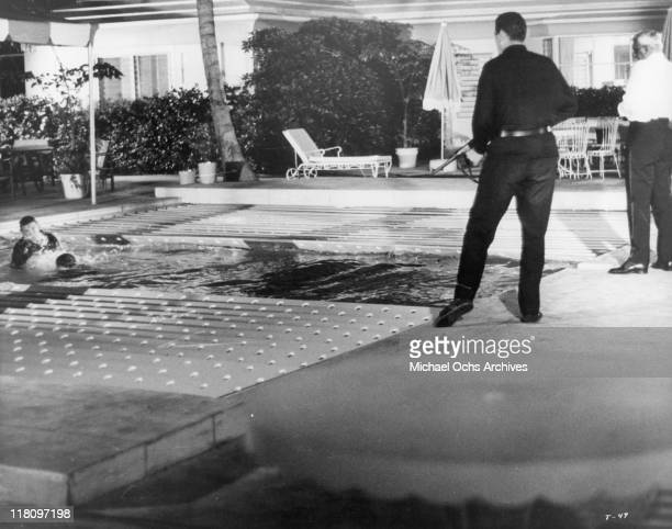 Actors fight in pool while actor with gun watches in a scene from the film 'Thunderball' 1965