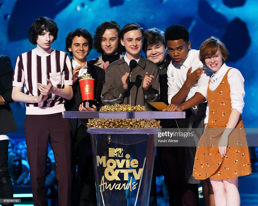 Actors Finn Wolfhard, Jack Dylan Grazer, Wyatt Oleff, Jaeden Lieberher, Jeremy Ray Taylor, Chosen Jacobs, and Sophia Lillis accept the Best On-Screen Team award for 'It' onstage during the 2018 MTV Movie And TV Awards at Barker Hangar on June 16, 2018 in Santa Monica, California.