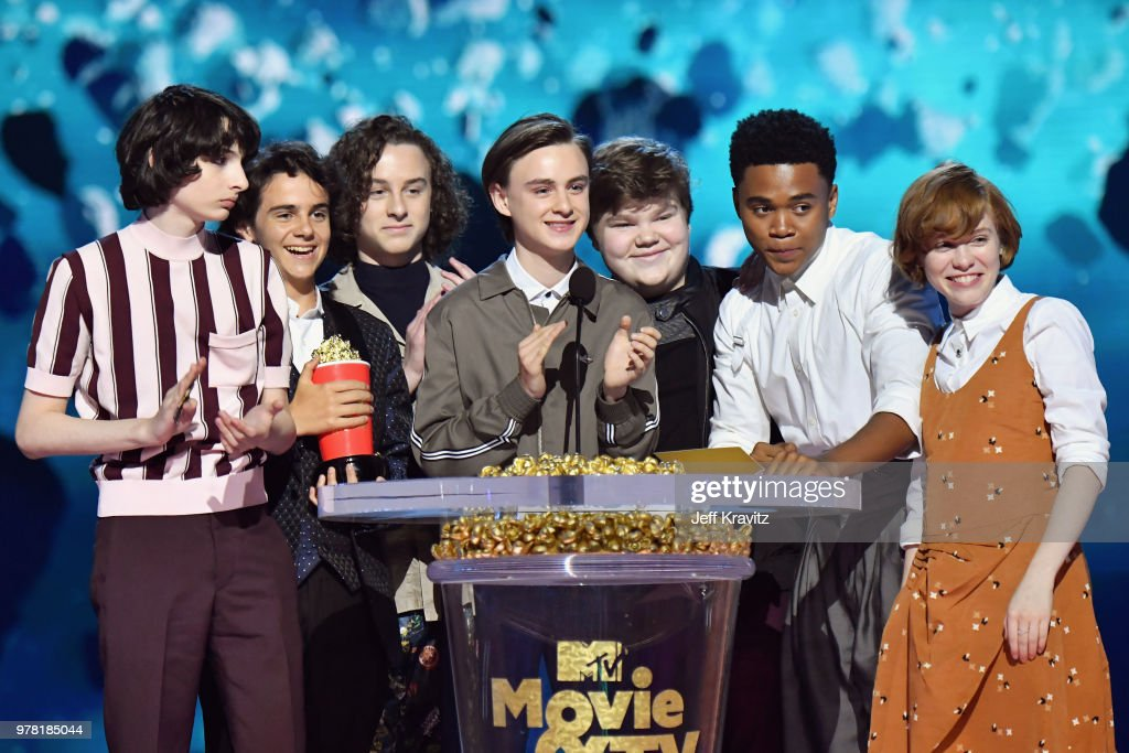 Actors Finn Wolfhard, Jack Dylan Grazer, Wyatt Oleff, Jaeden Lieberher, Jeremy Ray Taylor, Chosen Jacobs, and Sophia Lillis accept award onstage at the 2018 MTV Movie And TV Awards at Barker Hangar on June 16, 2018 in Santa Monica, California.