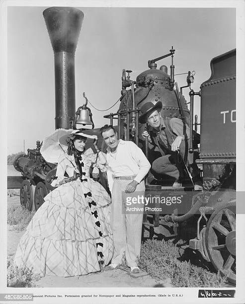 Actors Frances Dee and Joel McCrea with director Frank Lloyd on the set of the movie 'Wells Fargo' standing next to the railroad engine 'William...