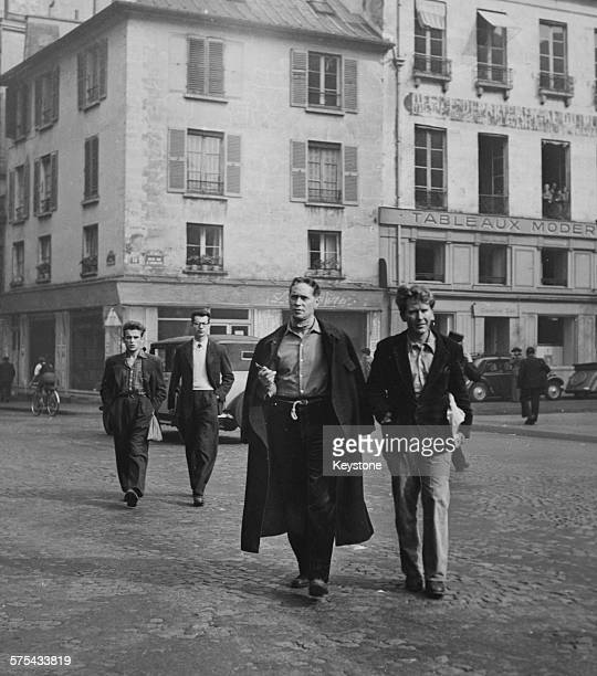 Actors Franchot Tone and Burgess Meredith walking through the old streets of Saint-Germain-des-Pres where they are filming scenes for the movie 'The...