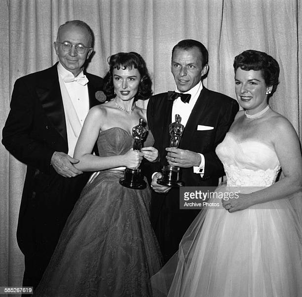 Actors Frank Sinatra and Donna Reed holding their supporting actor Oscars both for the film 'From Here to Eternity' with presenters Walter Brennan...