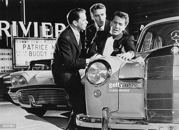 Actors Frank Sinatra and Peter Lawford support Richard Conte while Conte leans against a Mercedes Benz in a parking lot in Las Vegas Nevada in a...