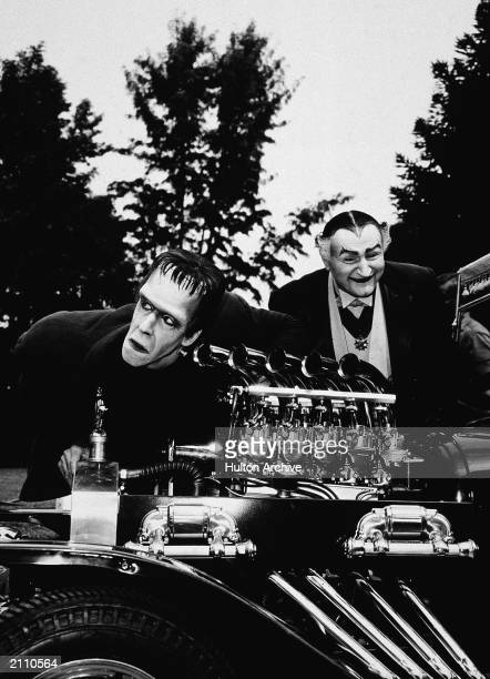 Actors Fred Gwynne and Al Lewis look at a dragster car engine in a still from the television series 'The Munsters' circa 1964