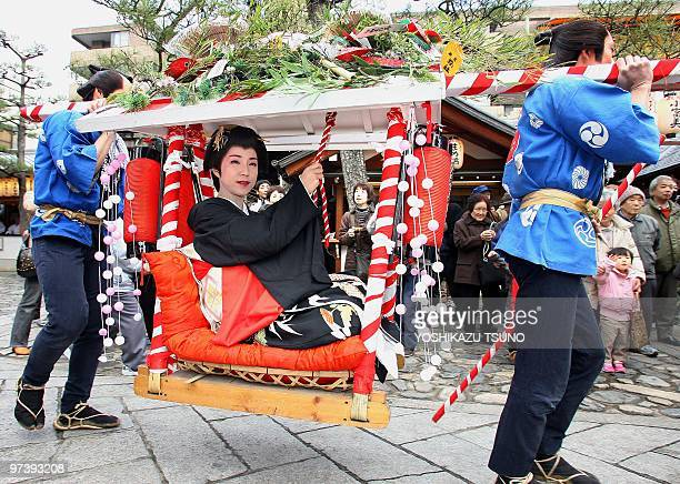 Actors from Toei Studio's Uzumasa Film Village theme park in traditional attire carry a geishaclad actress in a palanquin through the city of Kyoto...