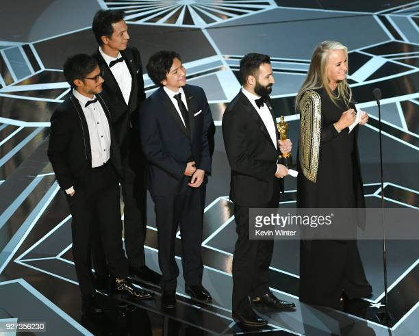 Actors Gael Garcia Bernal Benjamin Bratt and Anthony Gonzalez codirector Adrian Molina and producer Darla K Anderson accept Best Animated Feature...