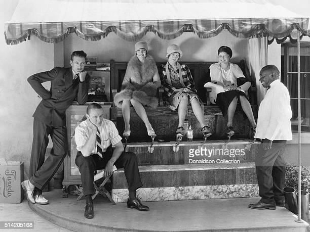 Actors Gary Cooper and Jack Luden wait for a shoe shine while actresses Louise Brooks Doris Hill and Thelma Todd get their shoes polished