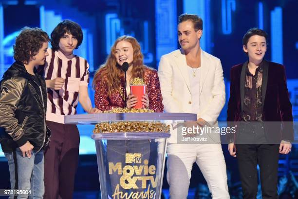 Actors Gaten Matarazzo Finn Wolfhard Sadie Sink Dacre Montgomery and Noah Schnapp speak onstage at the 2018 MTV Movie And TV Awards at Barker Hangar...